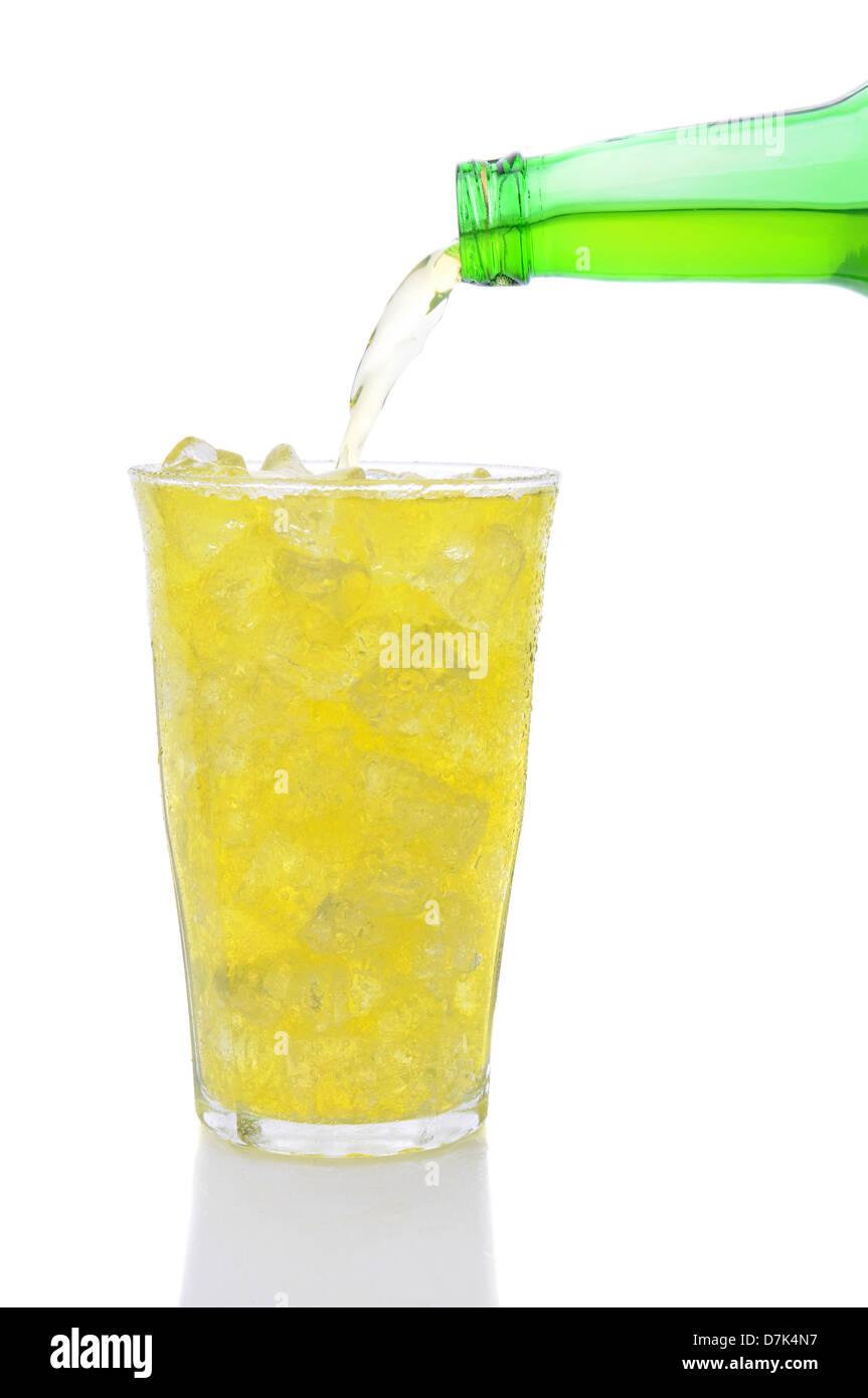 Una botella de Lemon Lime soda verterlo en un vaso lleno de cubitos de hielo sobre un fondo blanco. Foto de stock
