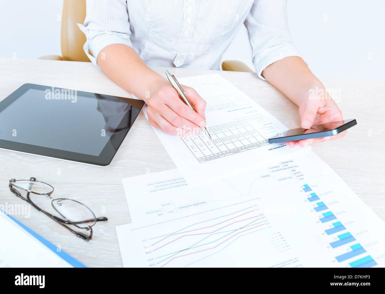 Exitosa empresaria sentados frente al escritorio en ropa casual y utilizando los dispositivos modernos para analizar Foto de stock