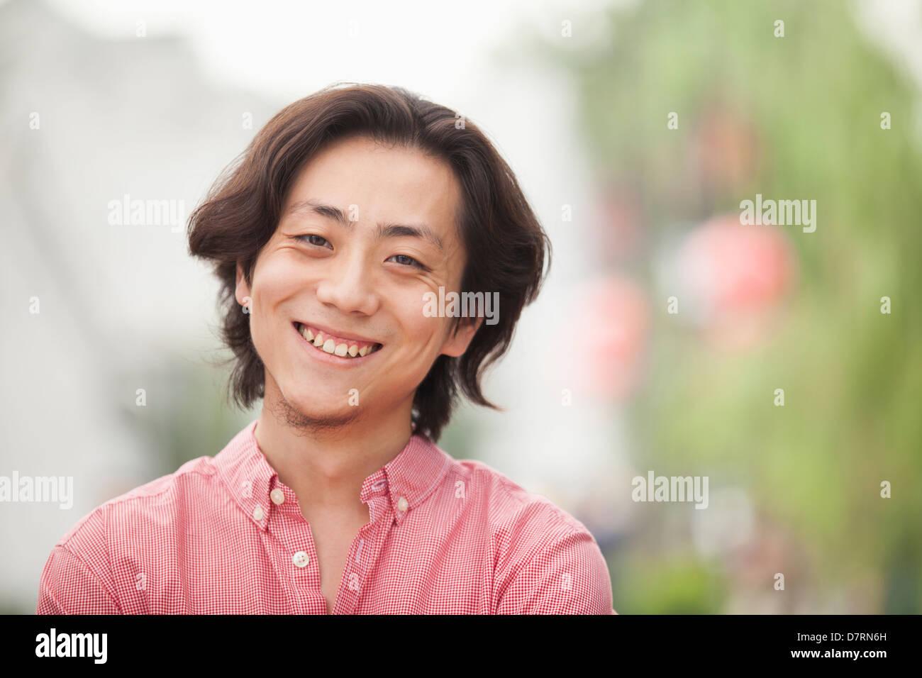 Sonriente joven con cabellos largos en Nanluoguxiang, Beijing, China Imagen De Stock