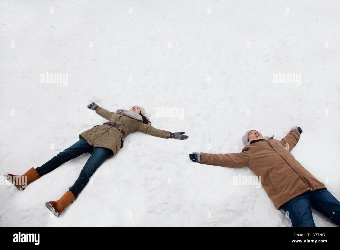 Pareja joven tendido en la nieve haciendo ángeles de nieve Imagen De Stock