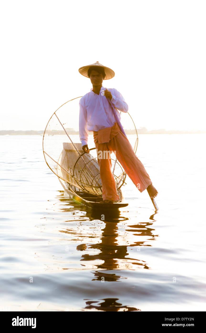 Pierna Intha pescadores remando al atardecer en el Lago Inle, Lago Inle, el Estado de Shan, Birmania Imagen De Stock
