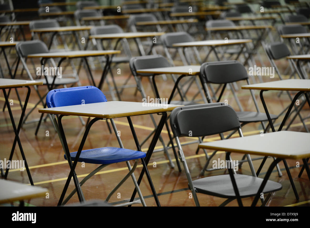 Escritorios establecidos en una sala escolar en preparación para el examen tablas vacías Foto de stock