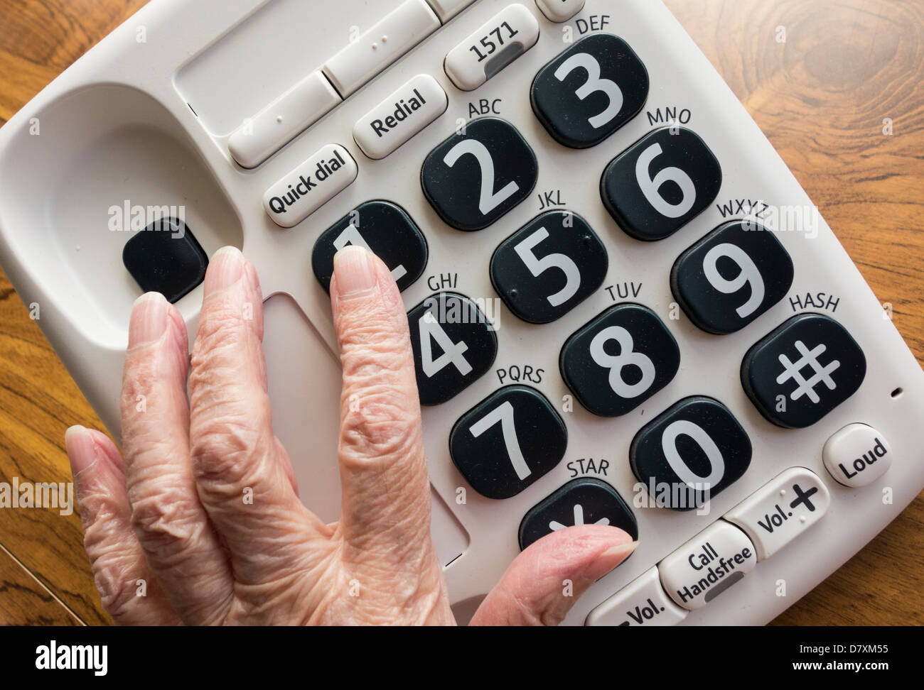 Anciana con visión disminuida pulsando el número 1 en gran botón teléfono Imagen De Stock