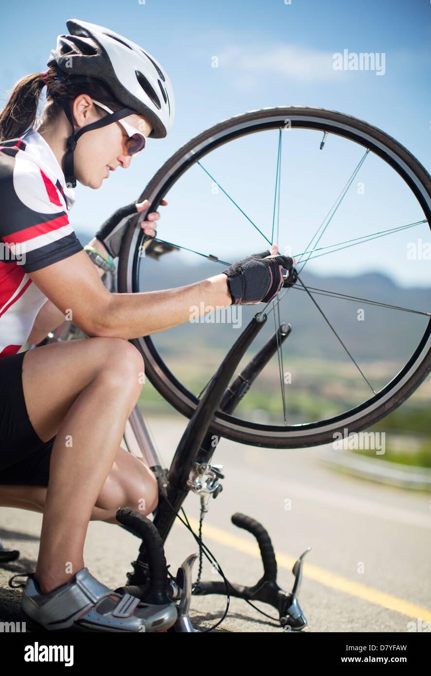 Ciclista ajustar el neumático en carretera rural Imagen De Stock