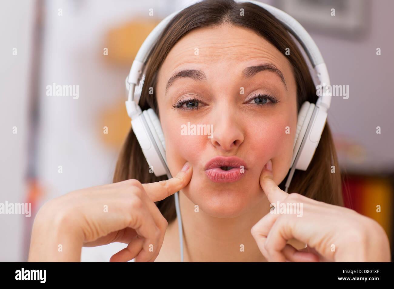 Atractiva chica disfruta de la música a través de auriculares, en sofá Imagen De Stock