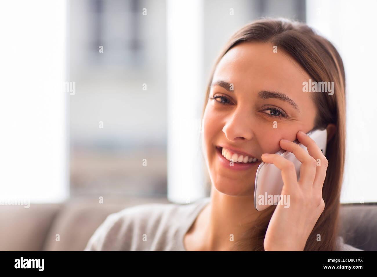 Bastante joven con blanco teléfono inteligente en su casa mirando la cámara Imagen De Stock