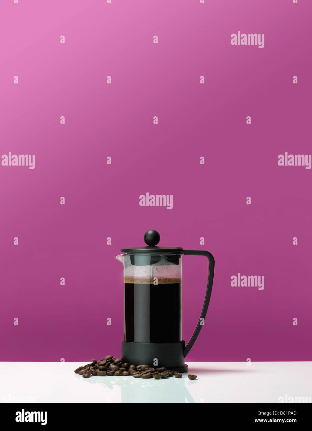 Cafetera cafetera sobre una mesa con granos de café contra un fondo de color rosa Foto de stock