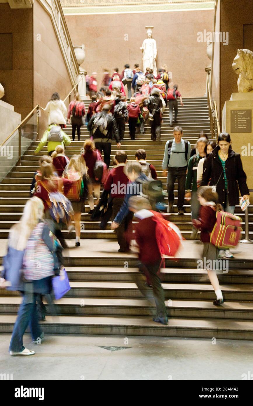 Niños entusiasmados en una excursión escolar tour rush hasta la escalera, el British Museum, Londres, Imagen De Stock