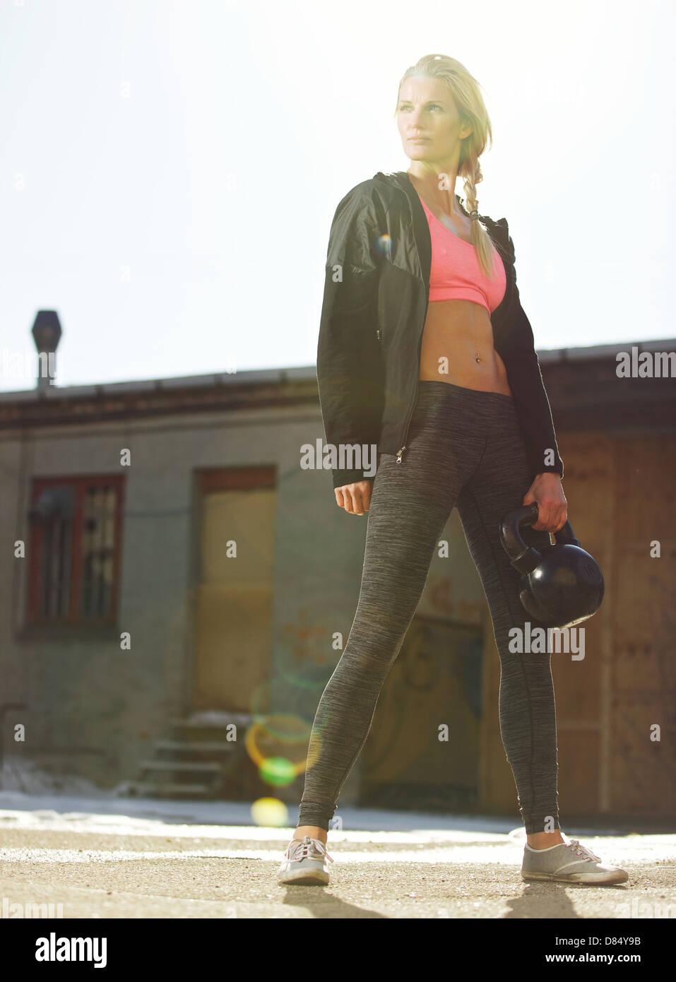 Crossfit atractiva mujer sosteniendo un kettlebell en ropa deportiva al aire libre Imagen De Stock