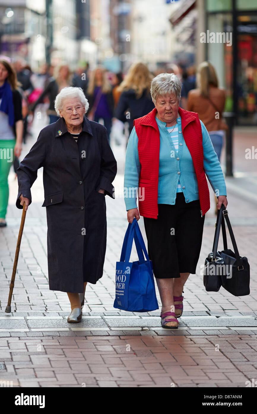 Senior Citizen mujer adulta y caminando en la calle comercial Grafton Street, Dublin, República de Irlanda Imagen De Stock