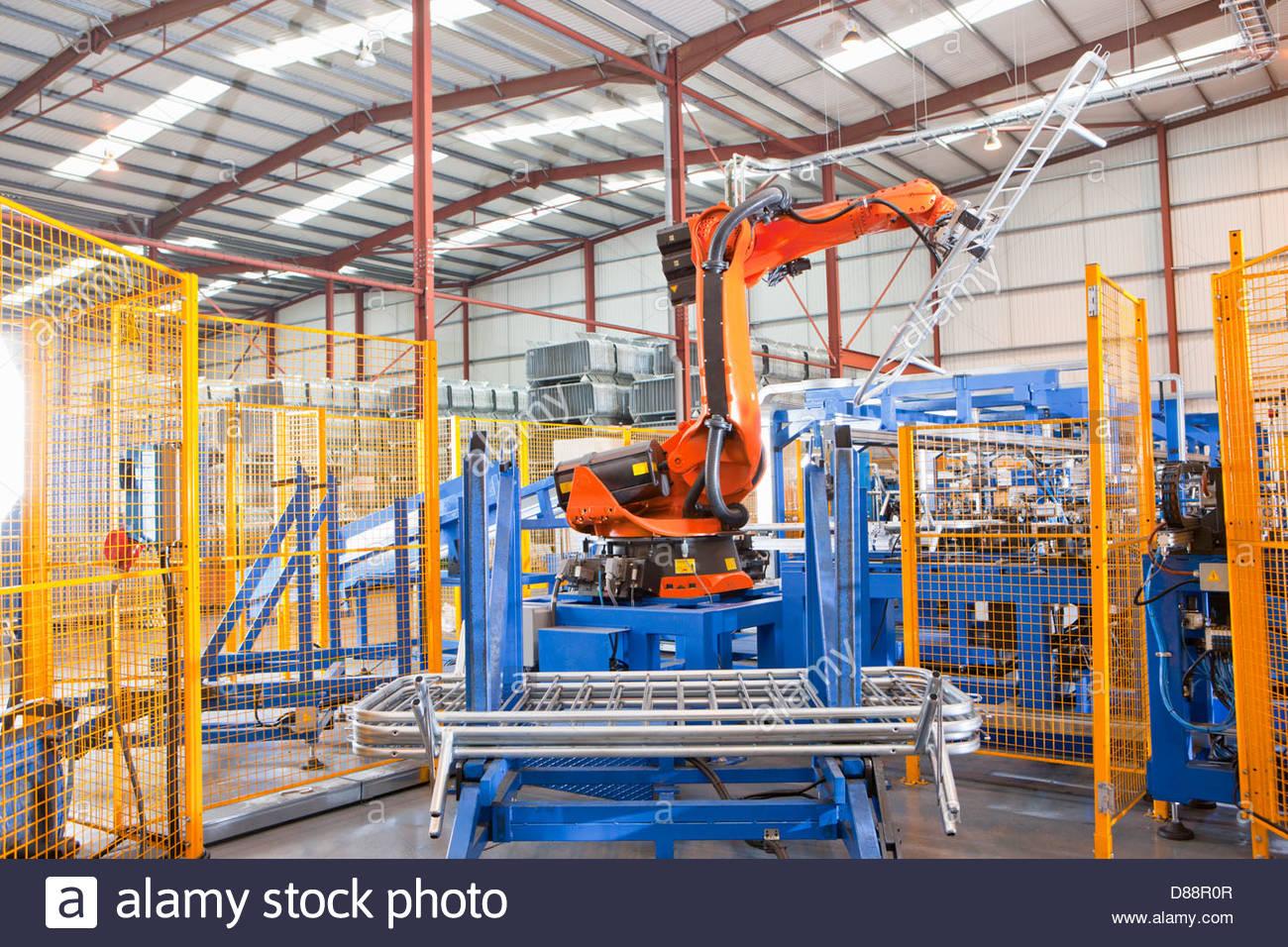 Mecanismo robótico levantar cercas de acero sobre la línea de producción en la planta de fabricación Imagen De Stock