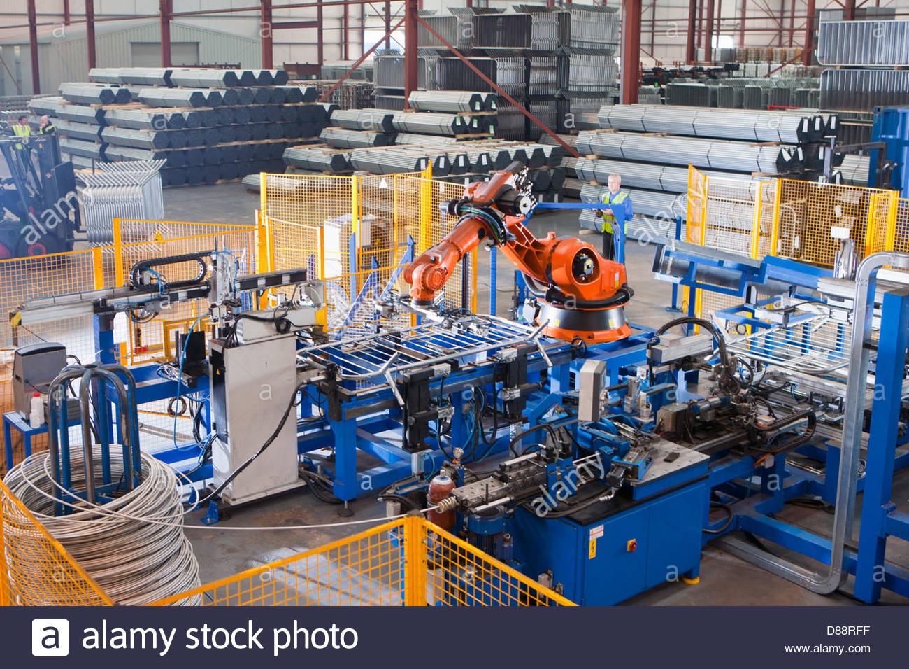 Trabajador controlar maquinaria robótica levantar cercas de acero sobre la línea de producción en Imagen De Stock