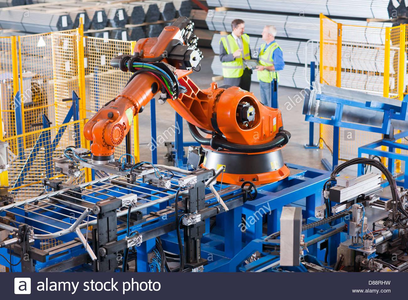 El empresario y el trabajador controlar maquinaria robótica levantar cercas de acero sobre la línea de Imagen De Stock