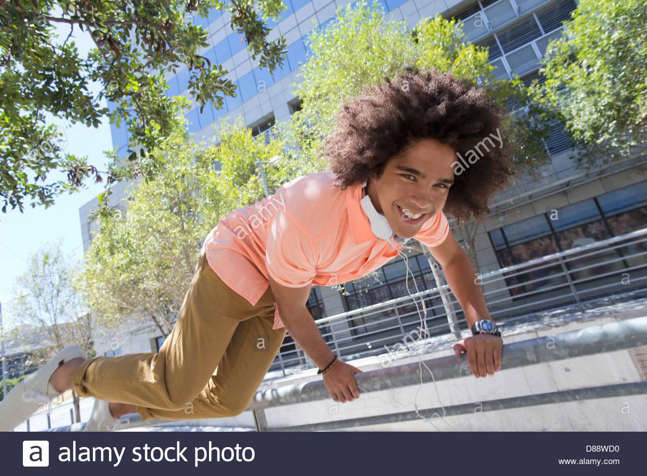 Retrato del joven sonriente saltar por encima de la baranda en la ciudad Imagen De Stock