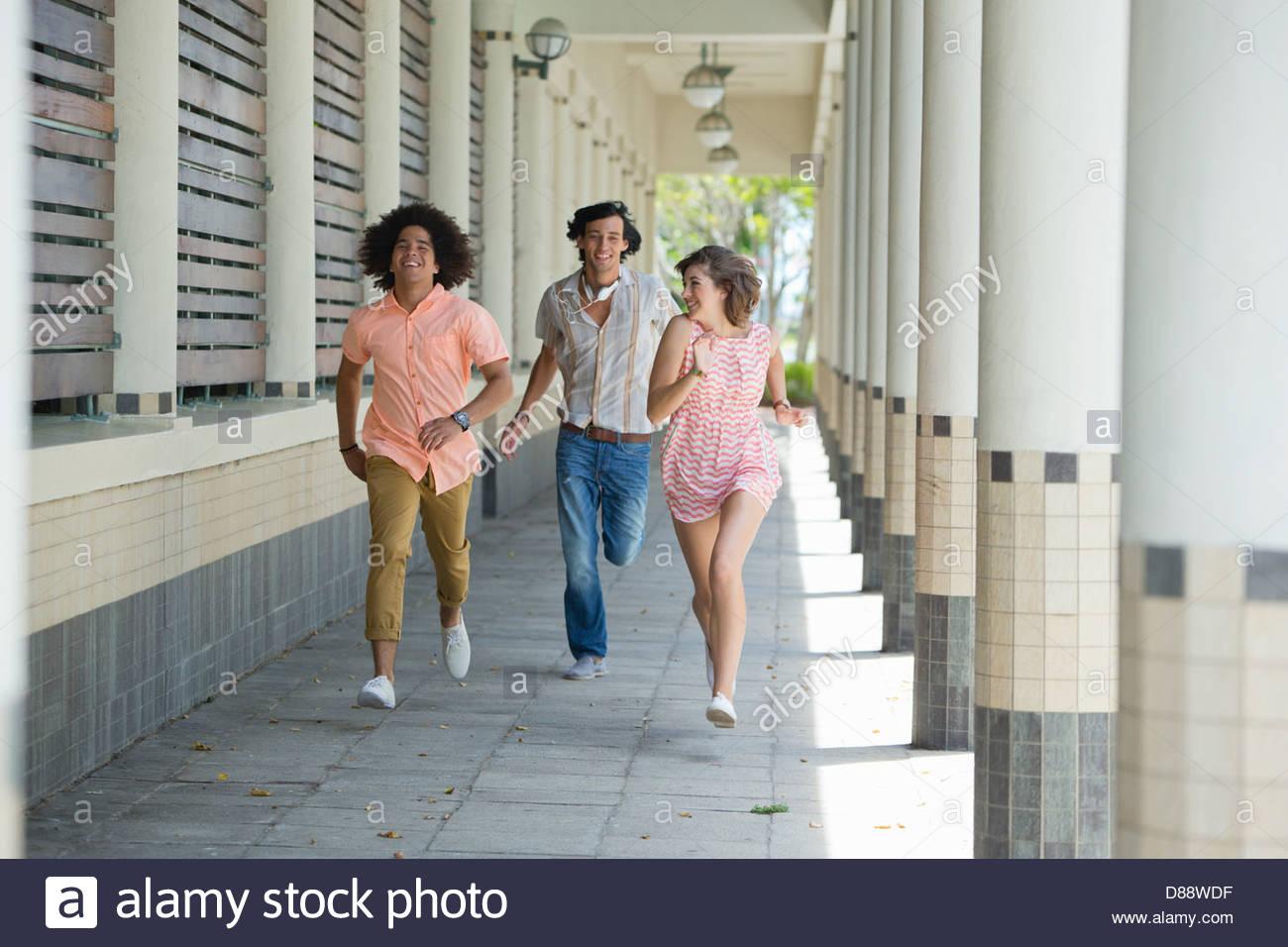 Sonriendo amigos corriendo a lo largo del corredor Imagen De Stock