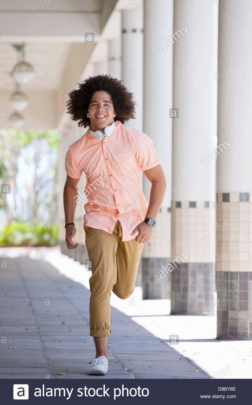 Retrato del joven sonriente que corre a lo largo de corredor exterior Imagen De Stock