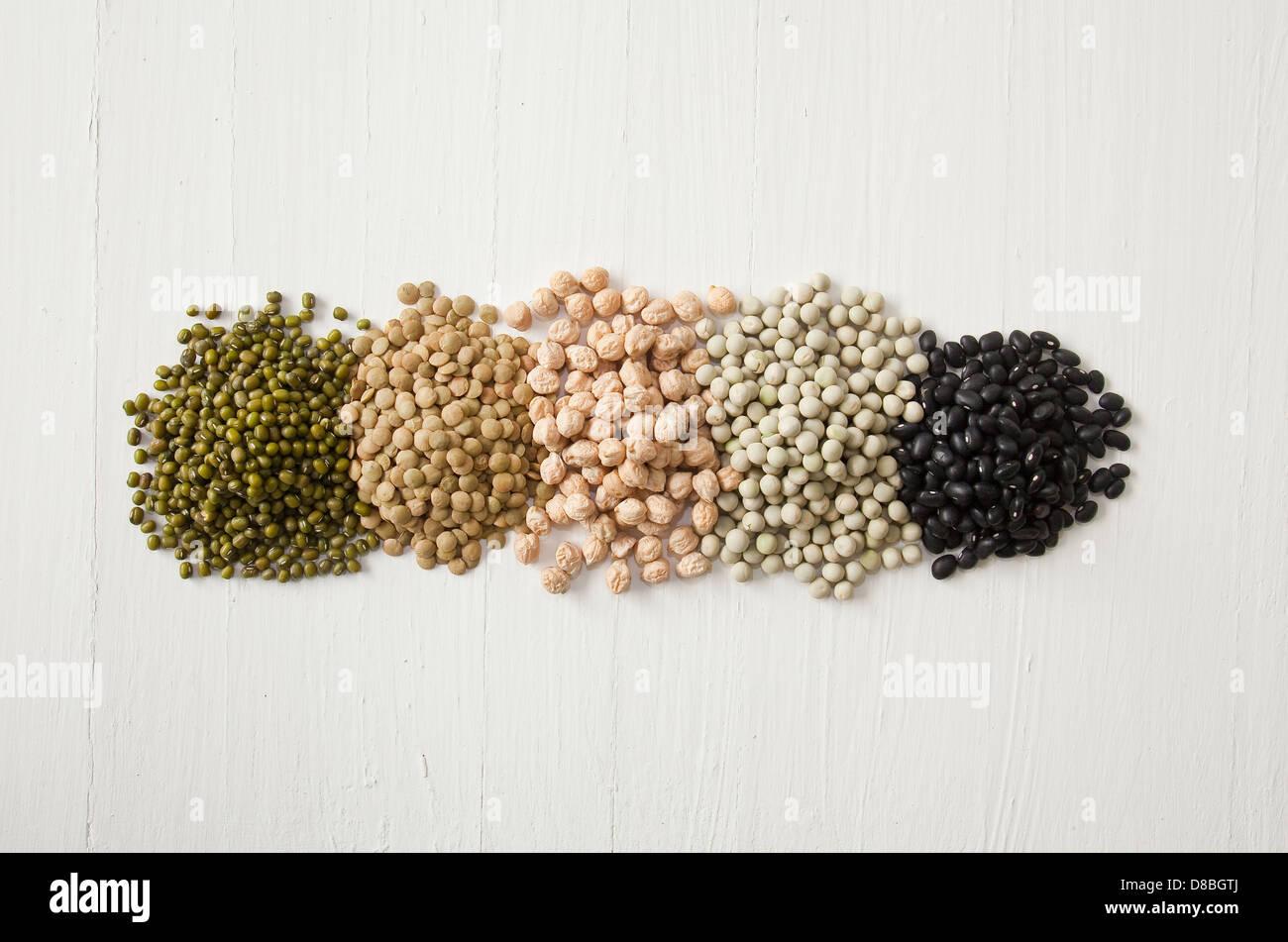 Montones de guisantes, habas, lentejas, coles y leguminosas en una línea sobre una superficie de madera rústica. Imagen De Stock