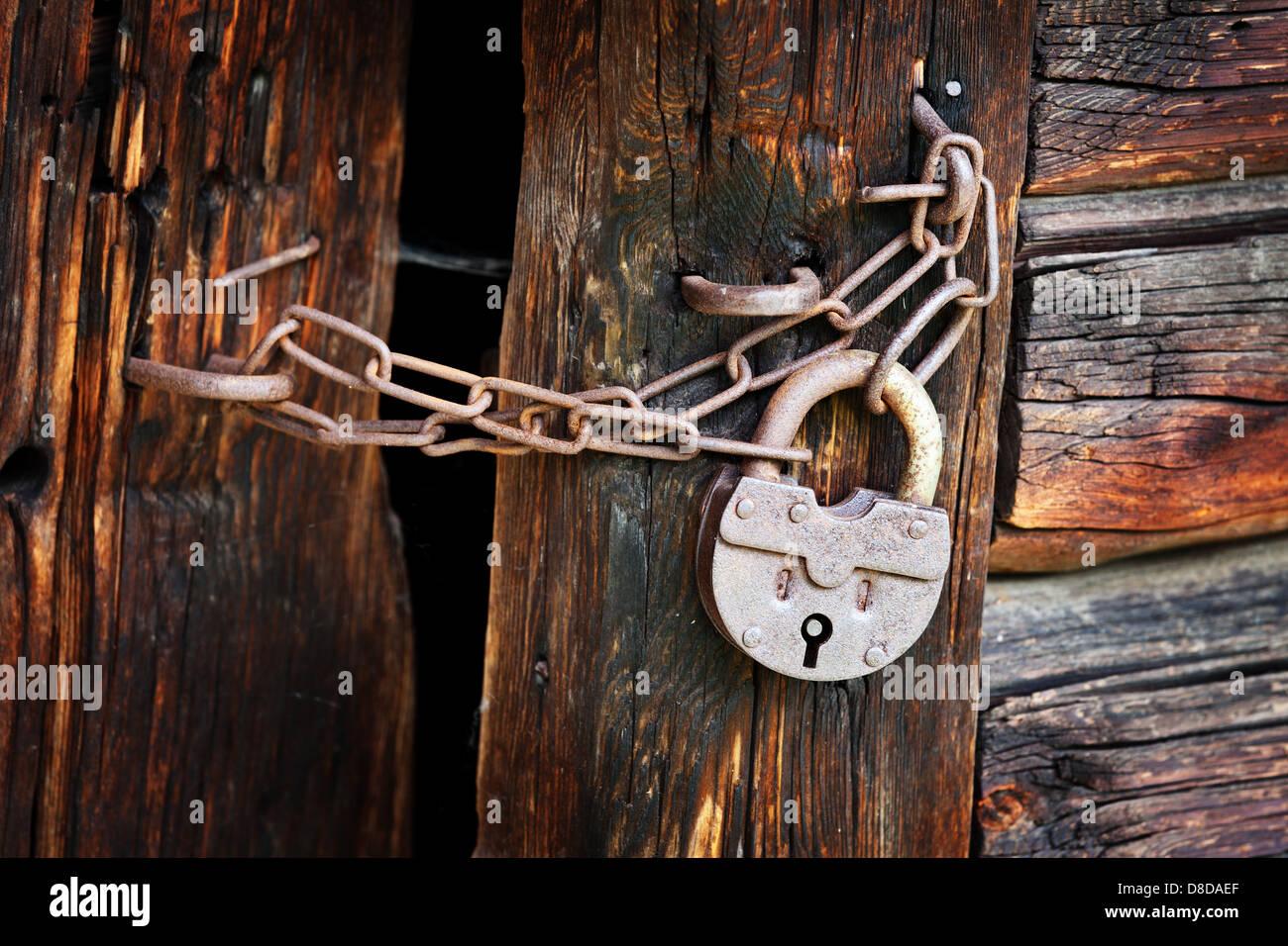 Oxidado viejo candado y cadena en la puerta de madera rural Foto de stock