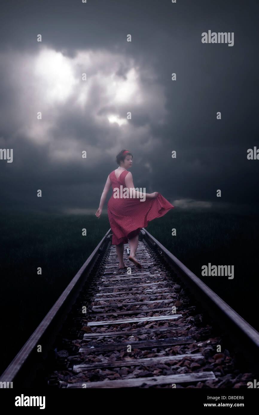 Una niña en un vestido rojo se está ejecutando en las vías del ferrocarril Imagen De Stock