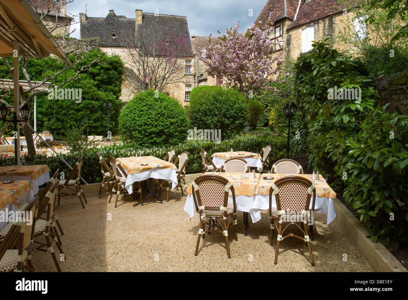 Patio para comer en un restaurante por edificios de piedra arenisca en el encanto medieval de Sarlat, Dordogne, Imagen De Stock