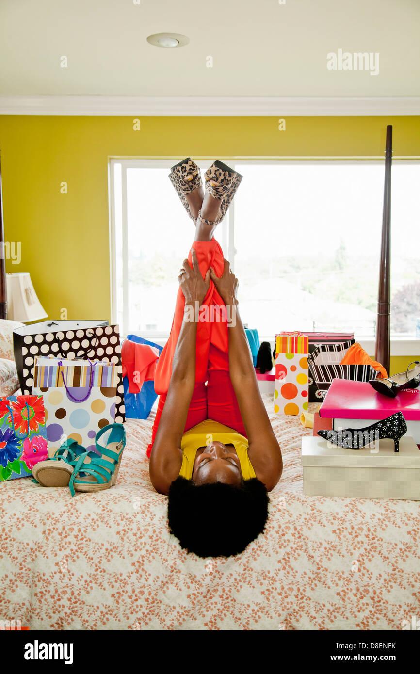 Mujer en la cama con los zapatos y bolsas de la compra. Foto de stock