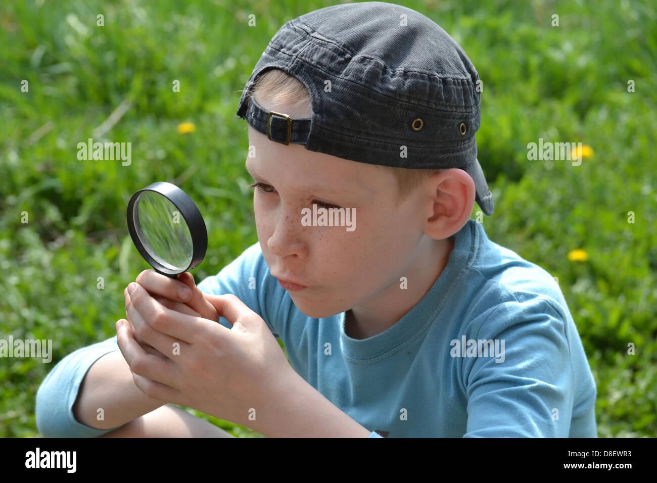 El adolescente observa a través de una lupa Foto de stock