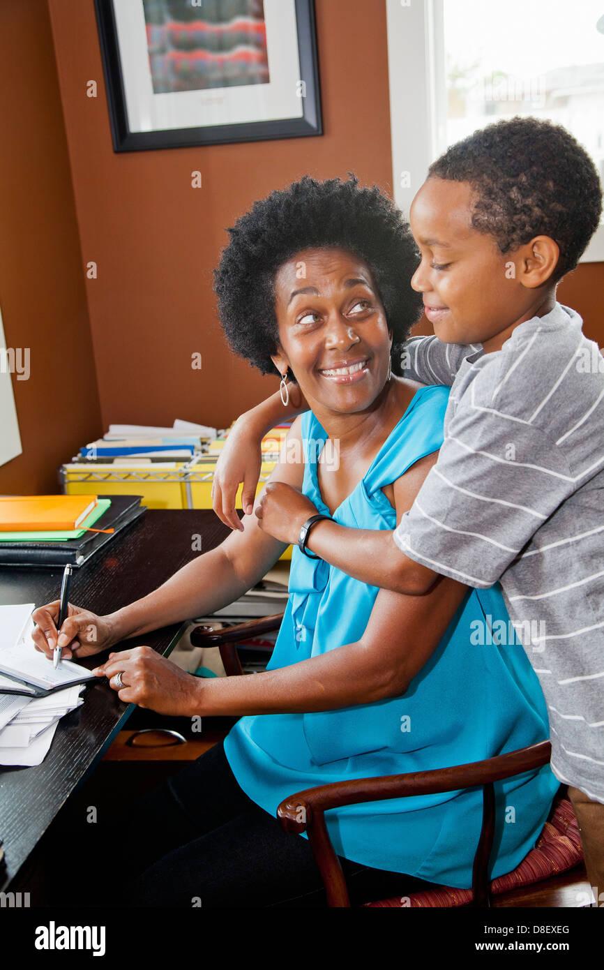 Mujer trabajando en su oficina doméstica con hijo Foto de stock