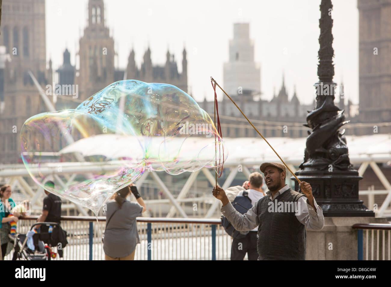 Los niños persiguiendo burbujas hechas por un artista de la calle en Londres del Banco del Sur. Imagen De Stock