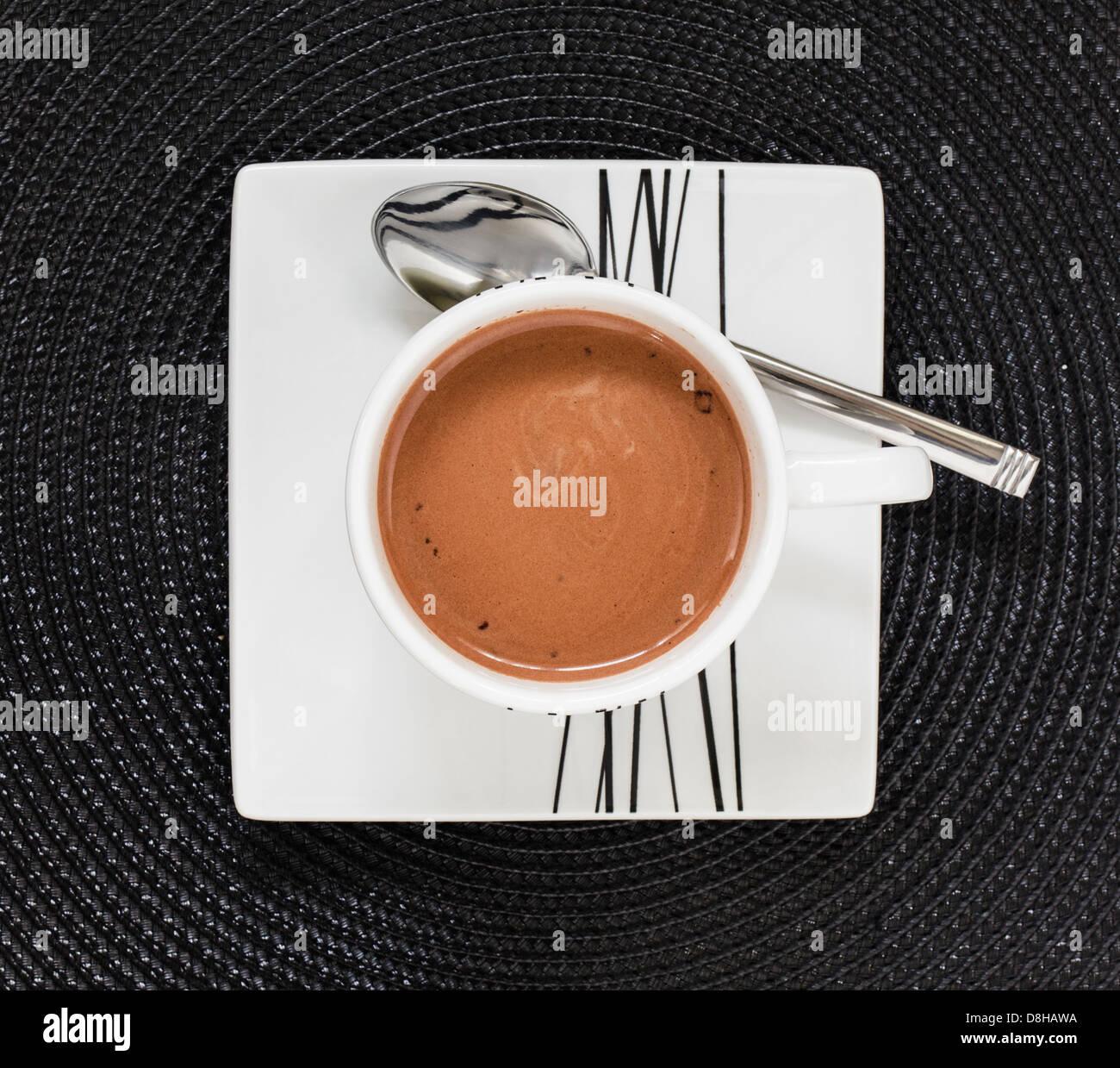 Bebida de chocolate caliente en taza y plato blanco sobre negro tablemat Foto de stock