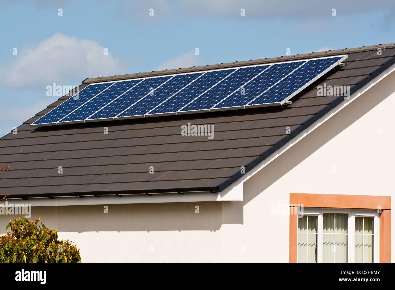 Los paneles solares fotovoltaicos, montados sobre un nuevo techo de tejas de una casa moderna Imagen De Stock