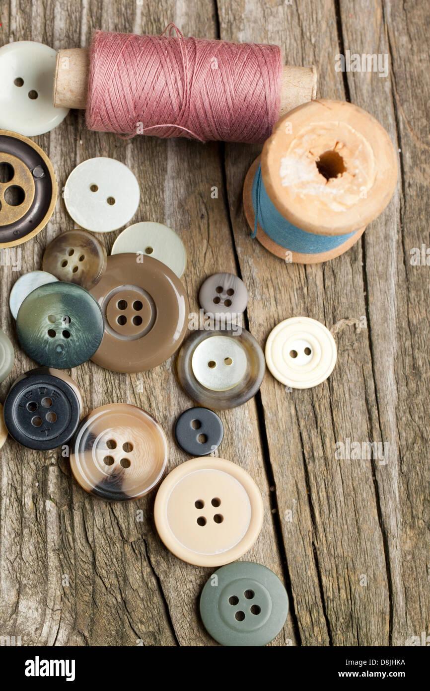 Carretes de hilos y botones en la mesa de madera antigua Foto de stock