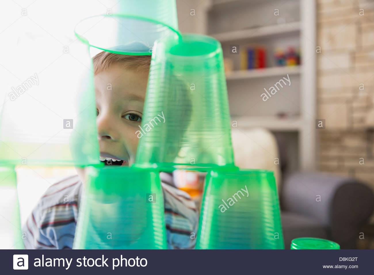 Chico sonriente jugando con vasos de plástico Imagen De Stock