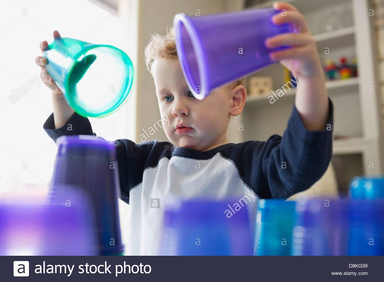 Joven apilar vasos de plástico en casa Imagen De Stock