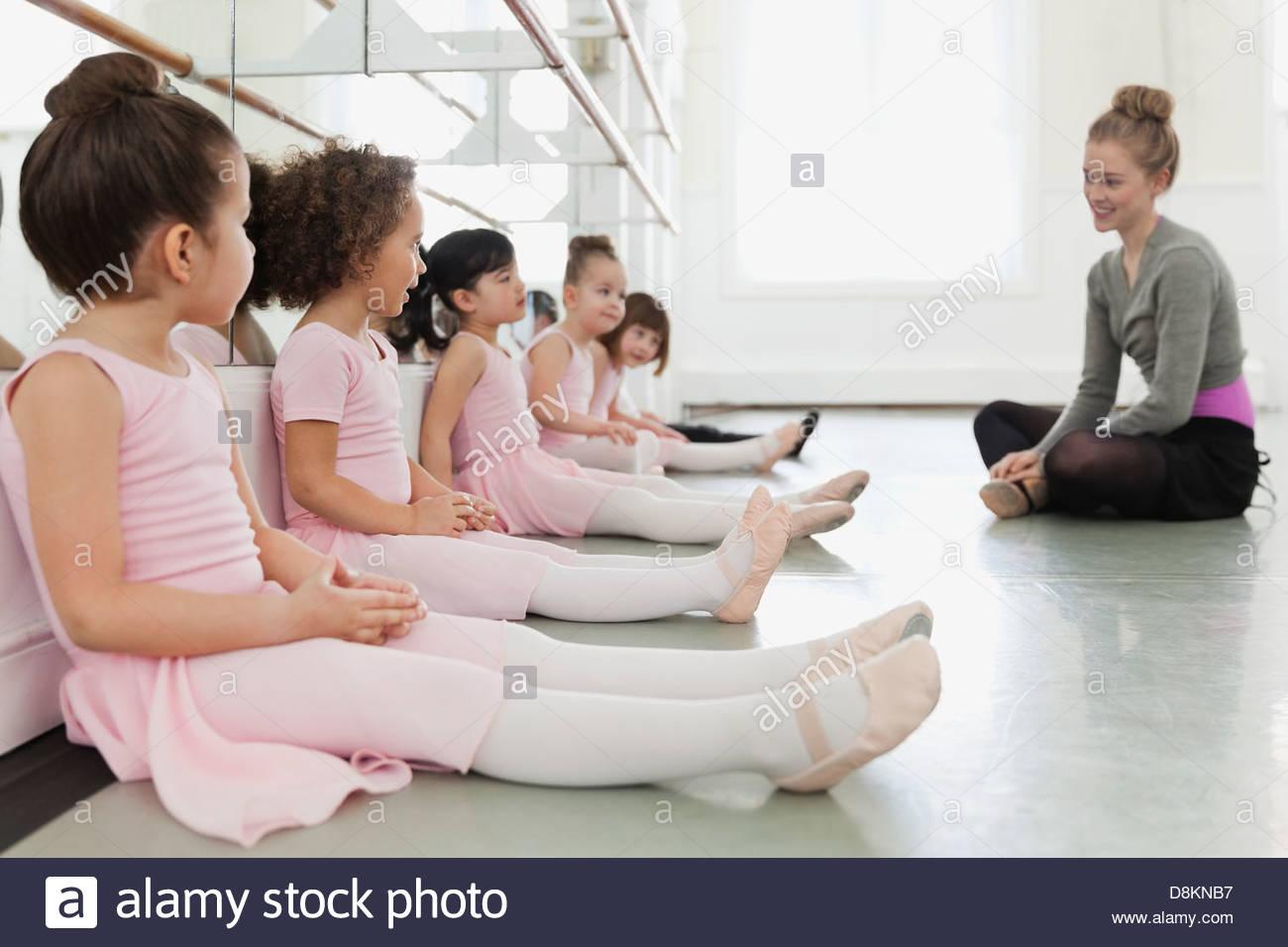 Instructor de ballet femenino con niños sentados en el piso en el ballet studio Imagen De Stock