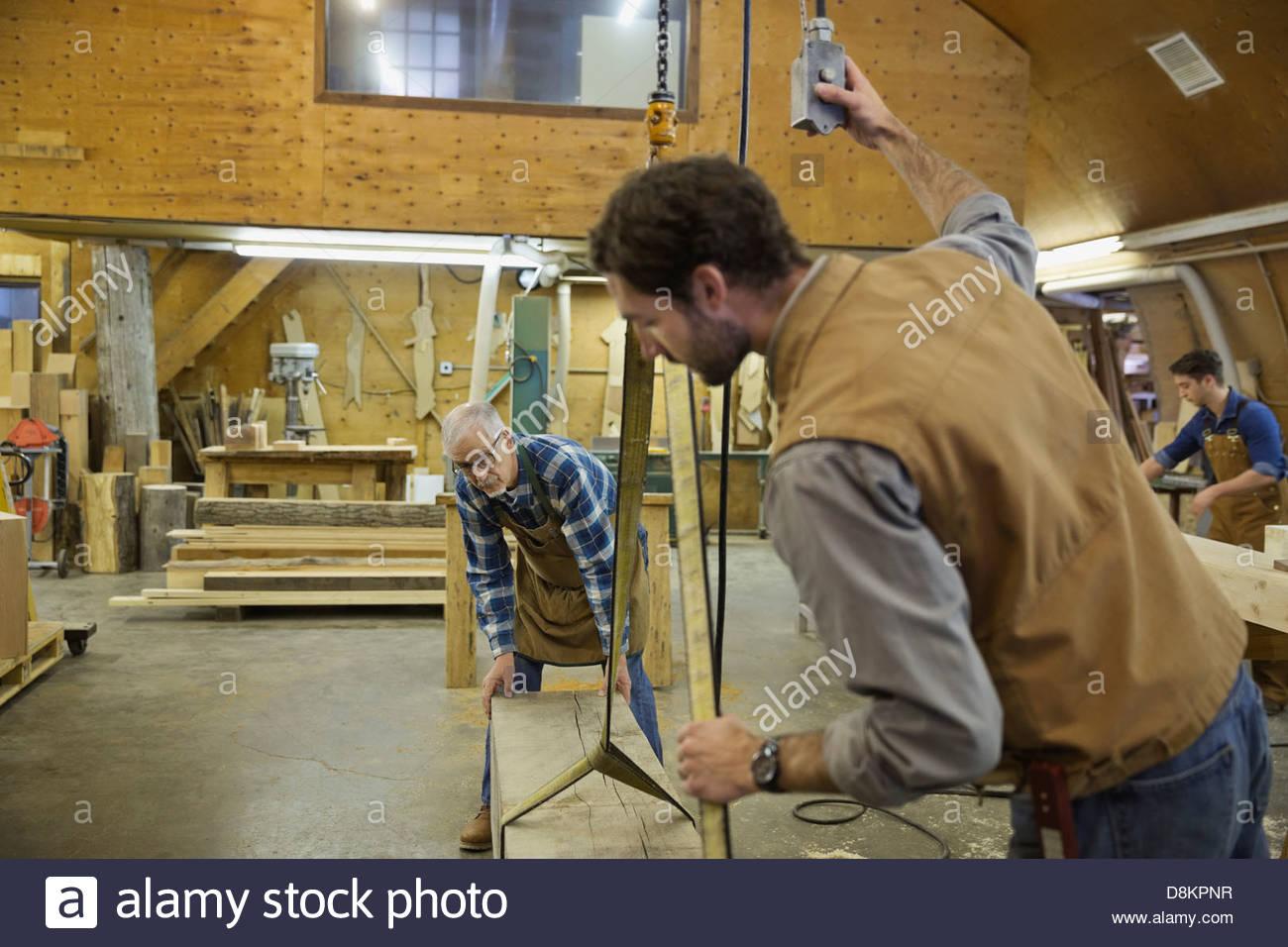 Ebanistas usando la grúa para mover la madera en el taller Imagen De Stock