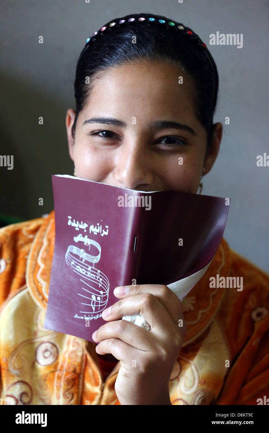 Egipto copto católico-cristiano, la educación religiosa, mujer cantando canciones cristianas en un hogar Imagen De Stock