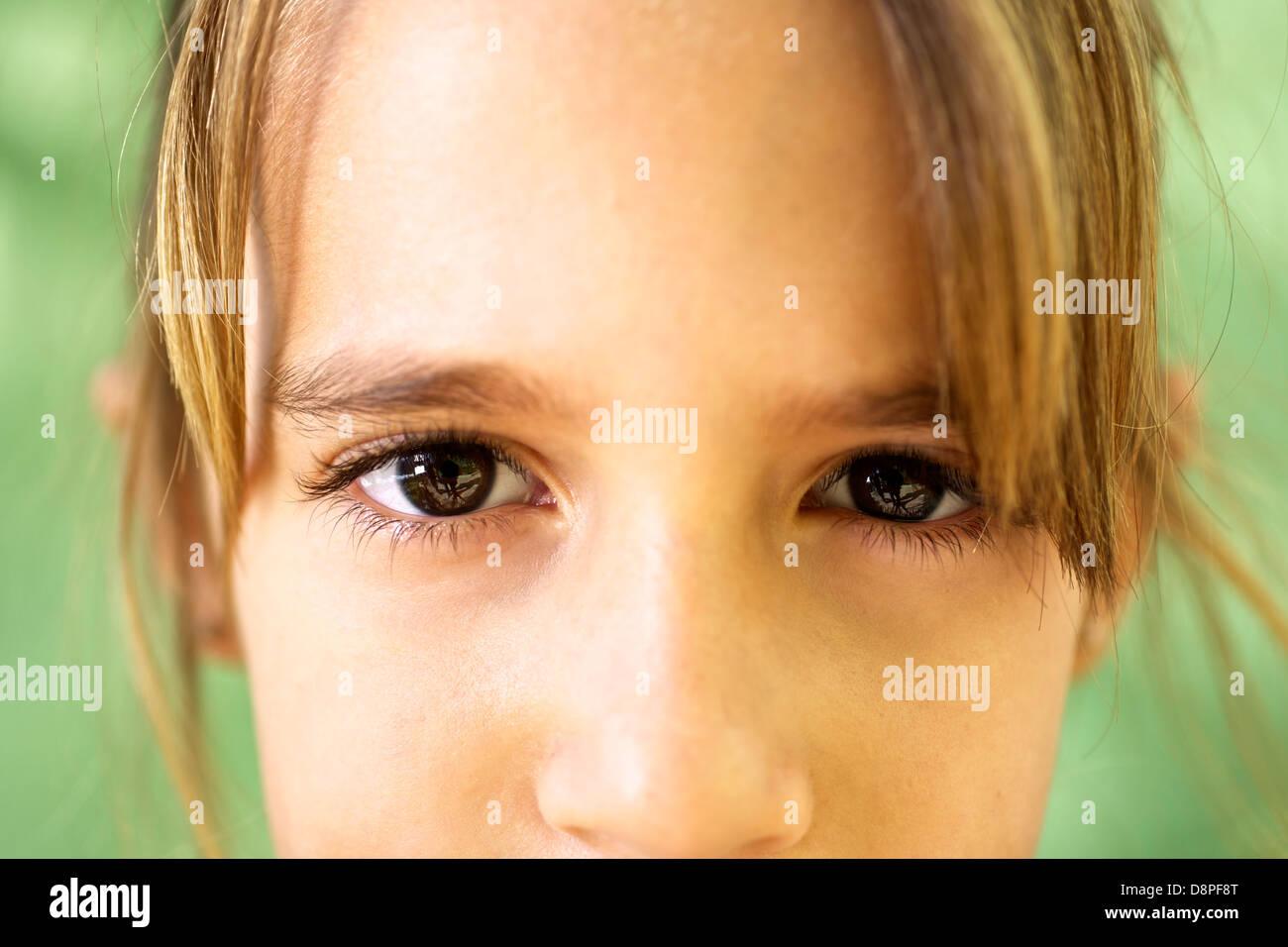 Los jóvenes y las emociones, retrato de niña seria mirando a la cámara. Primer plano de los ojos Foto de stock