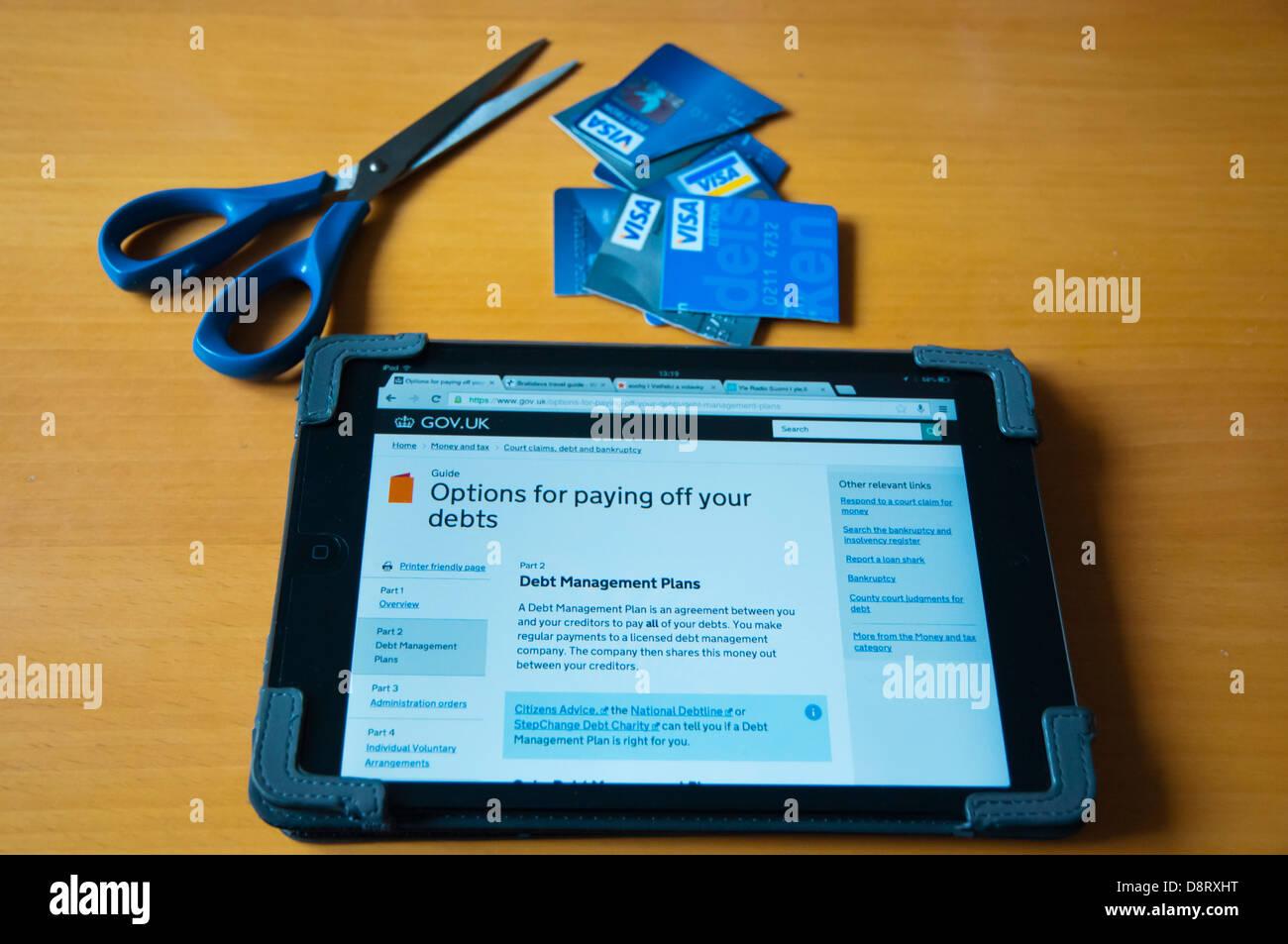 Persona mirando hacia el alivio de la deuda en el Reino Unido información sobre internet en el ipad mini tablet Imagen De Stock
