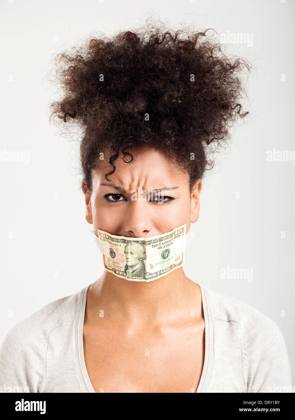 Afroamericana que cubre su boca con un billete de dólar, un gran concepto para las crisis globales Imagen De Stock