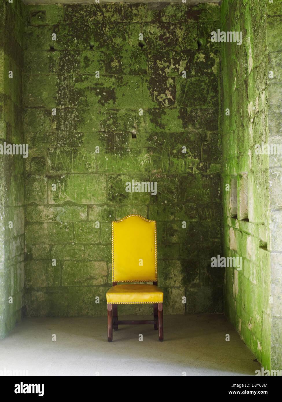 Una silla de color amarillo brillante contra un muro cubierto de líquenes. Imagen De Stock