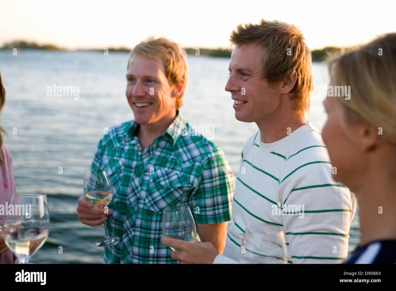 Tres personas riendo y bebiendo, Fejan, archipiélago de Estocolmo, Suecia. Foto de stock