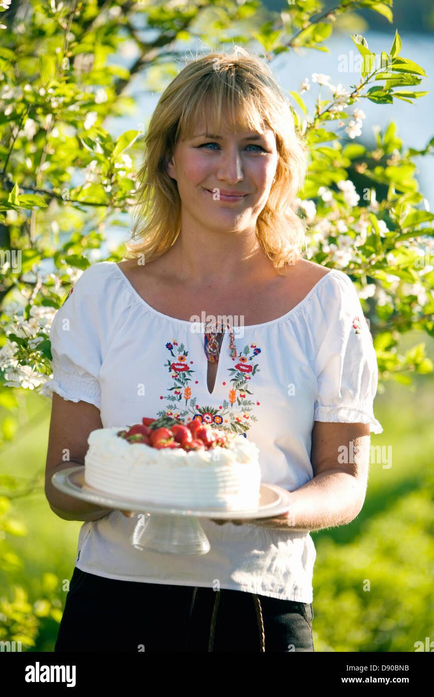 Mujer con una tarta de fresas, Fejan, archipiélago de Estocolmo, Suecia. Foto de stock
