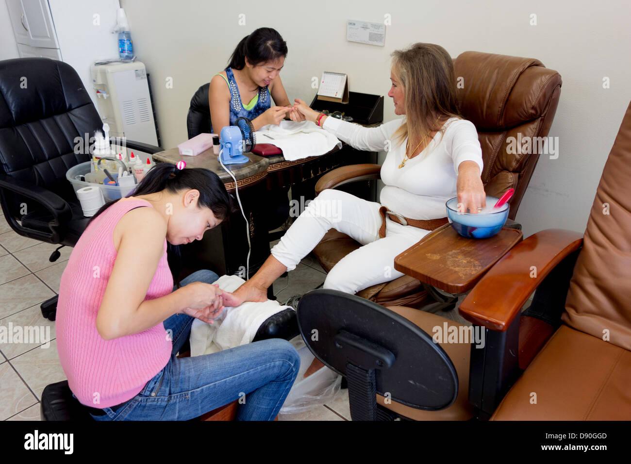 Mujer estadounidense obtiene la manicura y pedicura en propiedad vietnamita salón de uñas en Los Ángeles, el sur Foto de stock