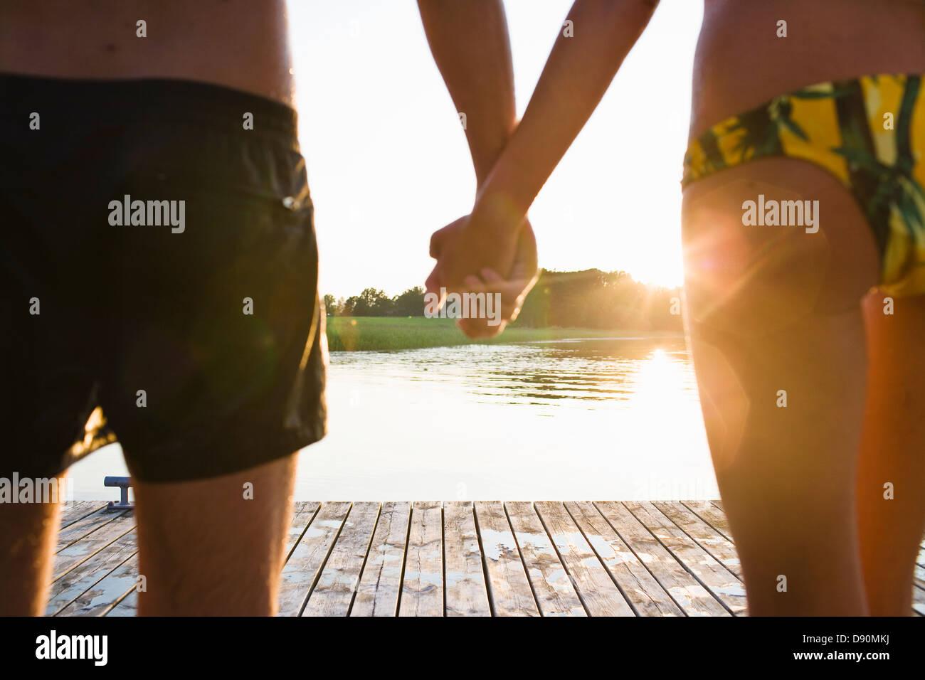 Par la celebración de manos en jetty Foto de stock