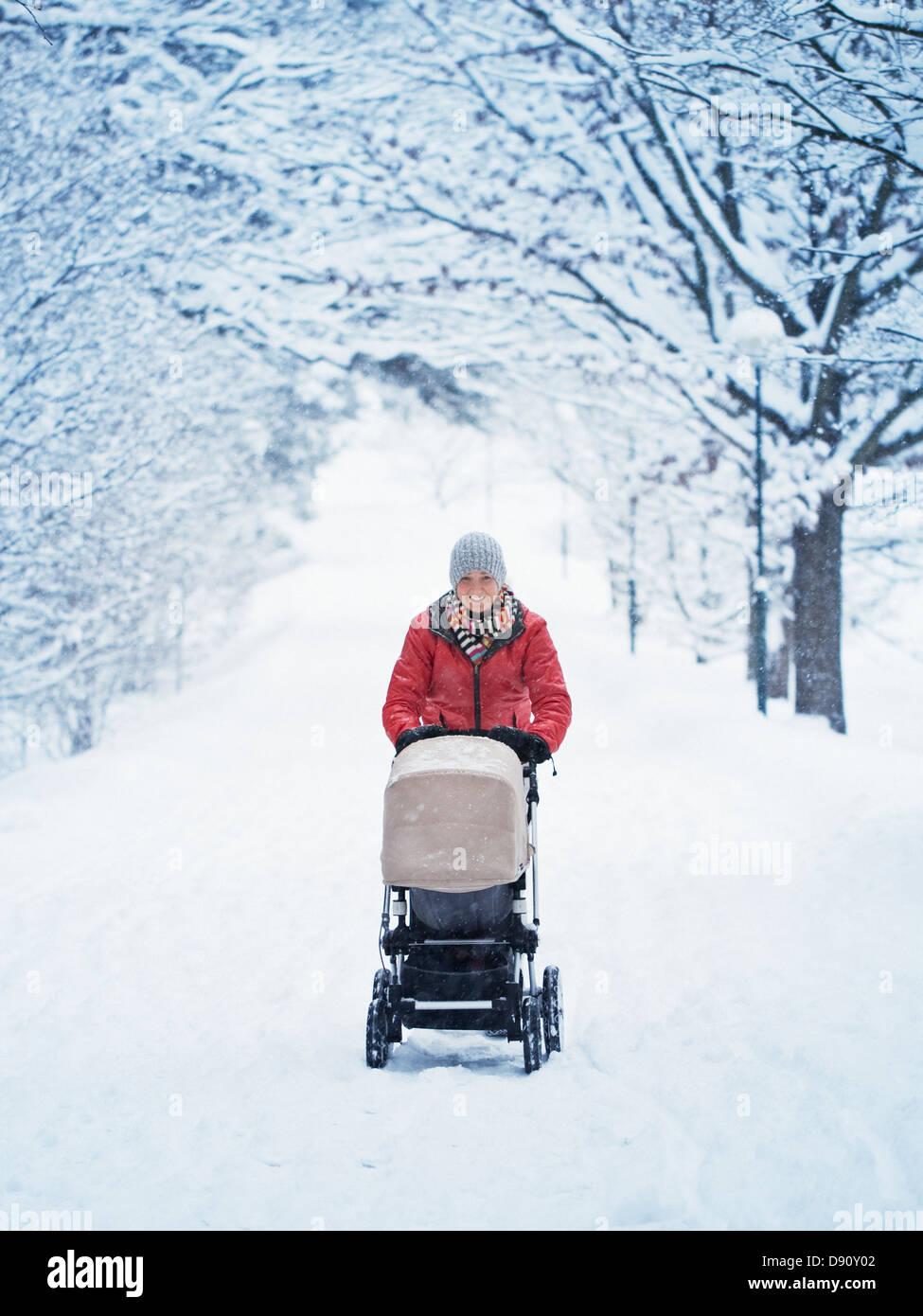 Madre sonriente caminando con pram al paisaje de invierno Imagen De Stock