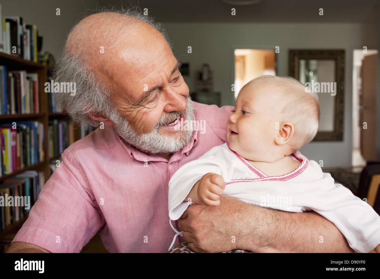 Hombre Senior y Bebé sonriendo en casa Imagen De Stock