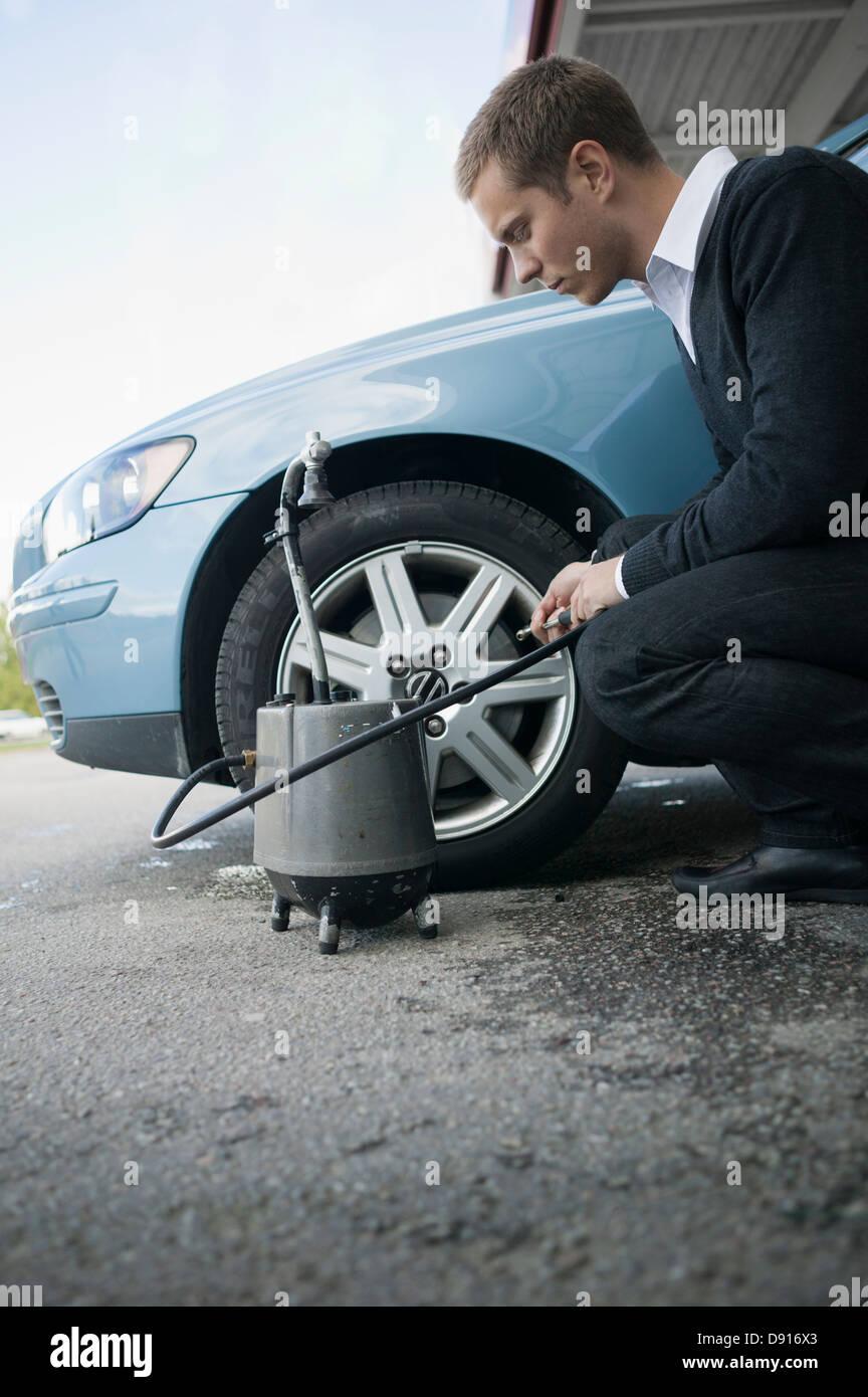Hombre, comprobación de la presión del aire en los neumáticos Imagen De Stock