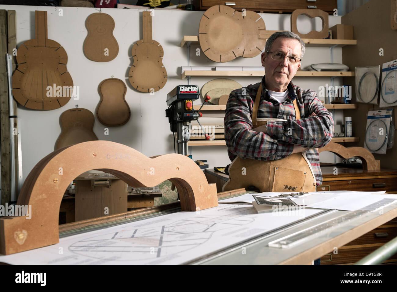 Creador de la guitarra por guitarra acústica permanente marco en el taller, Retrato Imagen De Stock