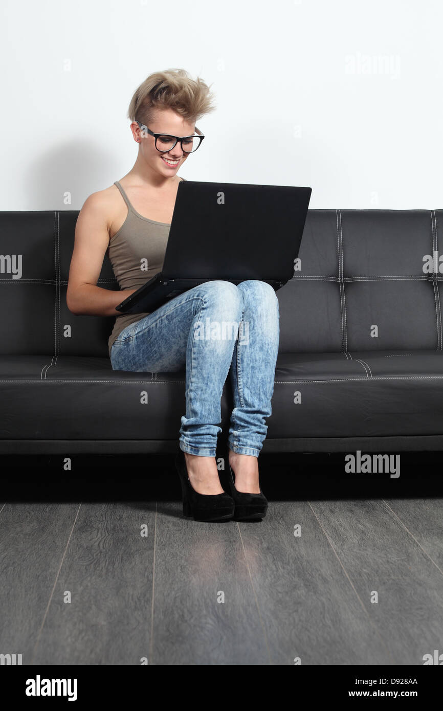 5f3b4bd5becf Moda joven con gafas en casa sentados en un sofá con un portátil Imagen De  Stock