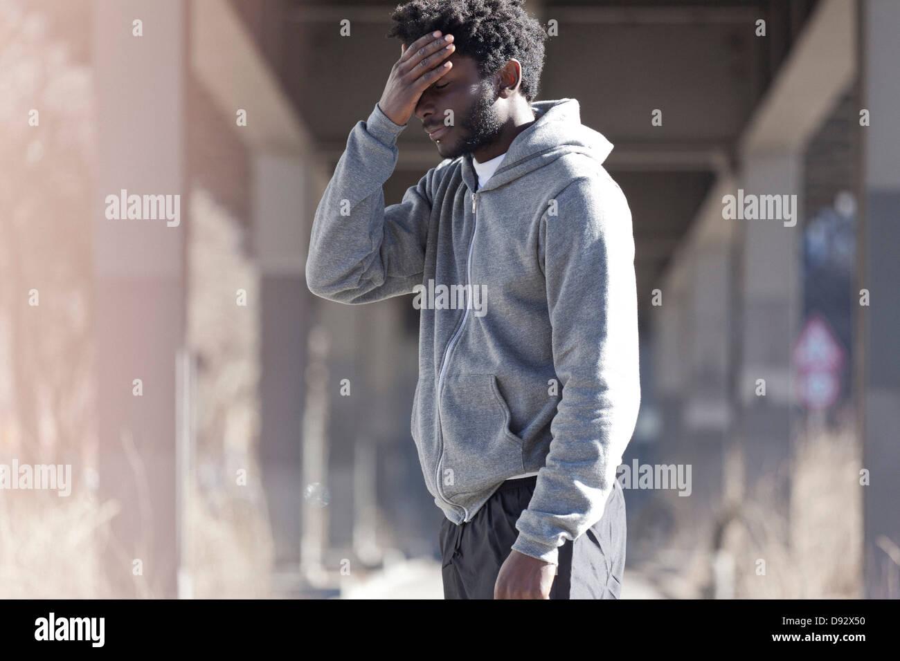 Un hombre con la mano en la frente con una mirada de abatimiento Imagen De Stock